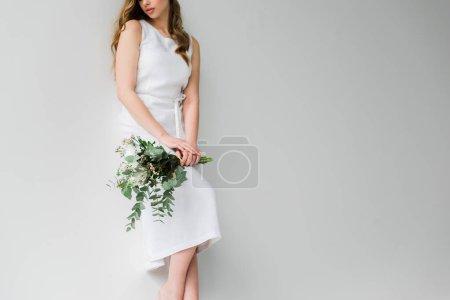 Photo pour Vue recadrée de la femme dans le bouquet de fixation de robe des fleurs avec des feuilles d'eucalyptus sur le blanc - image libre de droit