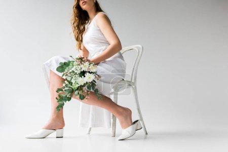 Photo pour Vue recadrée de la femme en robe assise sur une chaise et tenant un bouquet de fleurs avec des feuilles d'eucalyptus sur blanc - image libre de droit