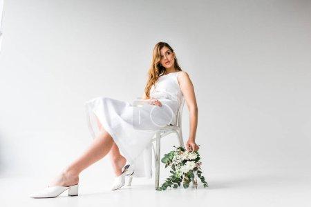 Photo pour Jeune femme en robe assis sur la chaise et tenant le bouquet de fleurs à l'eucalyptus feuilles blanc - image libre de droit