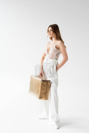 Photo for Stylish pretty girl holding suitcase while standing with hand in pocket on white - Royalty Free Image