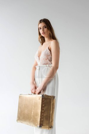 Photo for Beautiful young woman holding travel bag while standing on white - Royalty Free Image