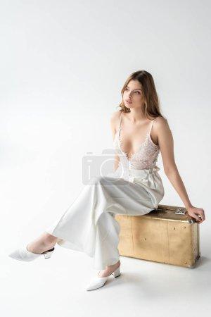Photo pour Rêveuse belle jeune femme assise sur un sac de voyage sur blanc - image libre de droit