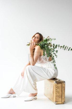 Foto de Moda niña sentada en la bolsa de viaje y con ramo de flores y eucalipto hojas en blanco - Imagen libre de derechos