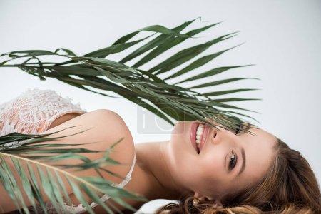 Photo pour Joyeuse jeune femme couchée près de feuilles de palmier tropicales sur blanc - image libre de droit