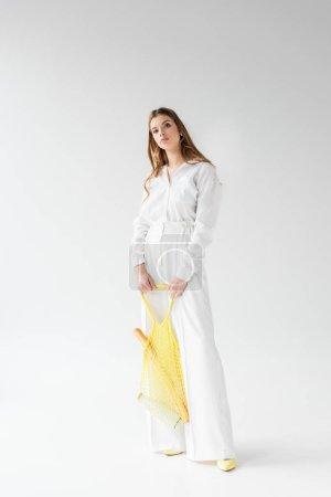 Photo pour Jolie jeune femme tenant sac à ficelle jaune avec baguette et bouteille de lait sur blanc - image libre de droit
