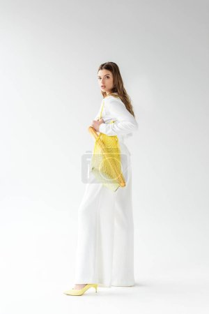 Photo for Young woman holding yellow string bag with baguette and bottle of milk on white - Royalty Free Image