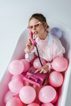 Photo for Overhead view of young woman in sunglasses talking on retro phone while lying in bathtub with pink air balloons on white - Royalty Free Image