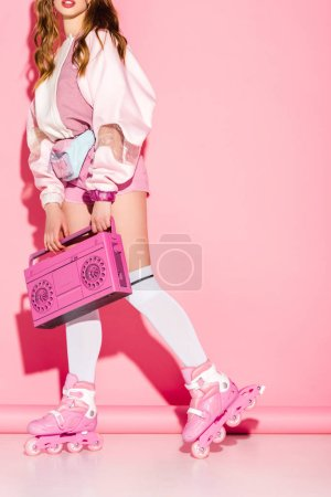 Photo for Cropped view of stylish girl holding retro boombox while standing in roller-skates on pink - Royalty Free Image