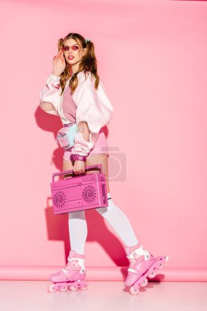 Photo for Stylish girl touching sunglasses and holding retro boombox while standing in roller-skates on pink - Royalty Free Image