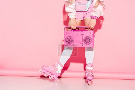 Photo for Cropped view of girl in long socks holding retro boombox on pink - Royalty Free Image