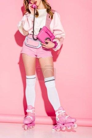 Foto de Vista recortada de chica elegante hablando por teléfono retro pie en patines en rosa - Imagen libre de derechos