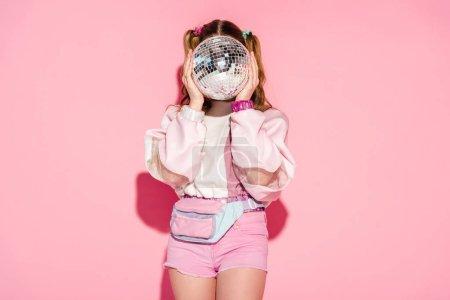 Photo pour Fille qui couvre le visage avec une boule disco brillante en se tenant debout sur la rose - image libre de droit