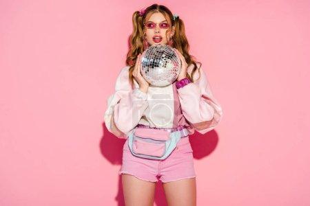 Foto de Chica sorprendida en gafas de sol con brillante bola de discoteca en rosa - Imagen libre de derechos