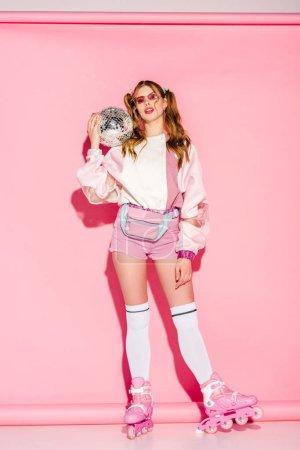 Foto de Chica atractiva en gafas de sol con bola de discoteca estando en patines en rosa - Imagen libre de derechos