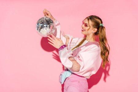 Photo pour Bonne humeur jeune femme regardant la boule disco rose - image libre de droit