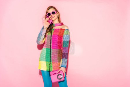Photo for Cheerful young woman in sunglasses and checkered dress talking on retro phone on pink - Royalty Free Image