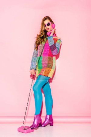 Photo for Surprised young woman in sunglasses and checkered dress talking on retro phone on pink - Royalty Free Image