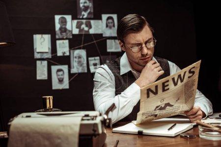 Foto de Detective concentrado en anteojos leyendo el periódico en la oficina oscura - Imagen libre de derechos