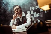 Low angle view of pensive detective in glasses smoking cigar in office