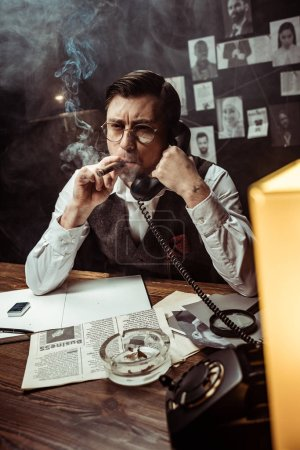 Photo pour Pensive detective in glasses talking on telephone in dark office - image libre de droit