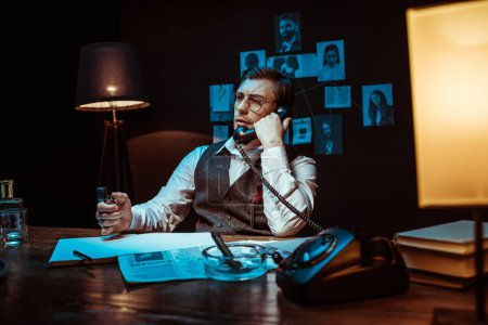 Photo for Pensive detective in glasses talking on telephone in dark office - Royalty Free Image