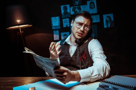 Photo for Concentrated detective in glasses holding newspaper and talking on telephone - Royalty Free Image