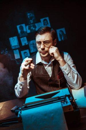 Foto de Detective Pensive en anteojos sosteniendo cigarros y mirando hacia fuera en el oscuro despacho - Imagen libre de derechos