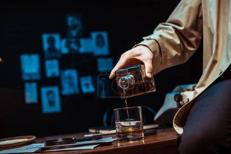 Foto de Partial view of detective pouring cognac in glass while sitting on table - Imagen libre de derechos