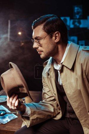 Photo pour Détective pensif dans des lunettes et un trench coat assis sur la table et tenant un chapeau - image libre de droit