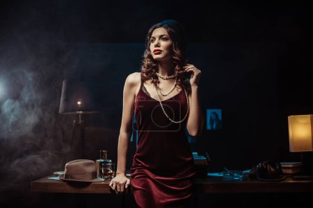 Photo for Dreamy woman in velvet dress looking away in dark office - Royalty Free Image