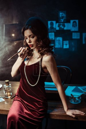 Photo for Woman in dress sitting on table and holding mouthpiece in dark office - Royalty Free Image