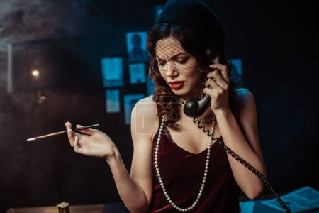 Photo for Sad attractive woman with mouthpiece talking on telephone in dark office - Royalty Free Image