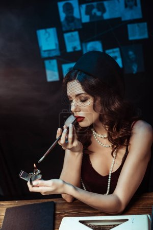 Foto de Hermosa mujer con boquilla de iluminación cigarrillo con encendedor en la oficina oscura - Imagen libre de derechos