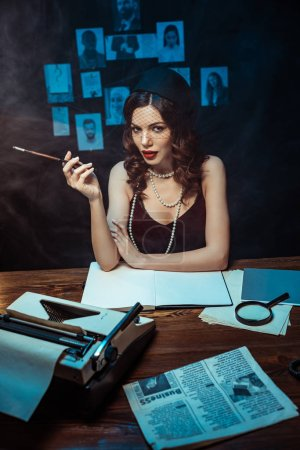 Photo for Pretty woman in dress with mouthpiece sitting at table with typewriter in dark office - Royalty Free Image