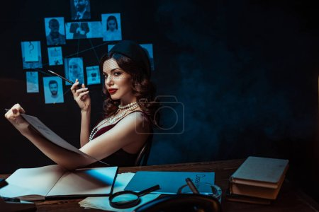 Photo for Serious woman with mouthpiece holding dossier and looking at camera in dark office - Royalty Free Image