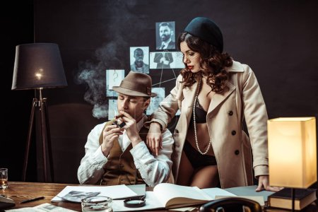 Photo for Sexy woman in underwear and trench coat seducing detective in office - Royalty Free Image