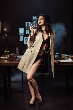 Photo for Sexy girl in black lingerie and trench coat holding mouthpiece in dark office - Royalty Free Image