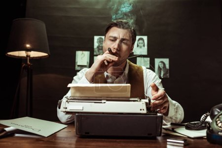 Photo for Detective smoking cigar and using typewriter in dark office - Royalty Free Image