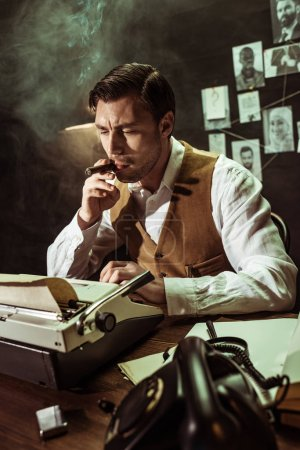 Photo for Pensive detective smoking cigar while using typewriter in dark office - Royalty Free Image