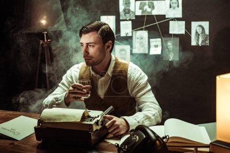 Photo pour Détective retenant le verre de Cognac tout en utilisant la machine à écrire dans le bureau sombre - image libre de droit