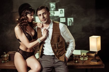 Photo for Sexy woman in black lingerie sitting on wooden table and flirting with detective in office - Royalty Free Image