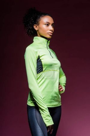 Photo for Beautiful african american sportswoman in track suit posing on dark - Royalty Free Image