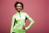 beautiful african american sportswoman in track jacket looking at camera and smiling isolated on pink