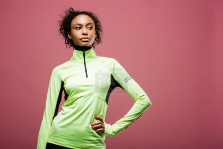 Photo for Beautiful african american sportswoman in track jacket posing with hand on hip isolated on pink with copy space - Royalty Free Image