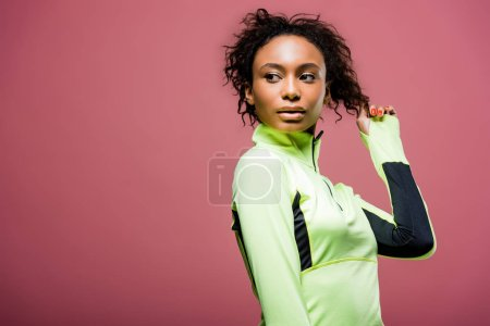 Photo for Beautiful african american sportswoman in track jacket posing isolated on pink with copy space - Royalty Free Image