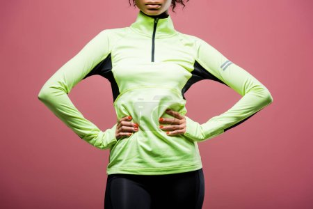 Photo for Cropped view of african american sportswoman in track jacket posing with hands akimbo isolated on pink - Royalty Free Image