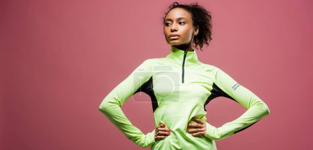 Photo for Panoramic shot of beautiful african american sportswoman in track jacket isolated on pink with copy space - Royalty Free Image