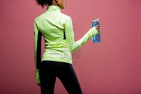 Photo for Back view of african american sportswoman in track jacket with sport bottle isolated on brown - Royalty Free Image