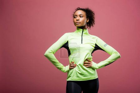 Photo for Beautiful african american sportswoman in track jacket with hands akimbo posing isolated on pink - Royalty Free Image