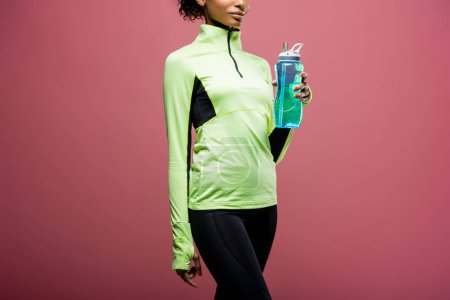 Photo for Partial view of african american sportswoman in track jacket with sport bottle isolated on brown - Royalty Free Image